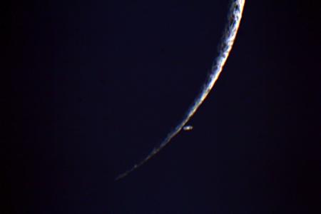 Saturn apareixent darrera la lluna