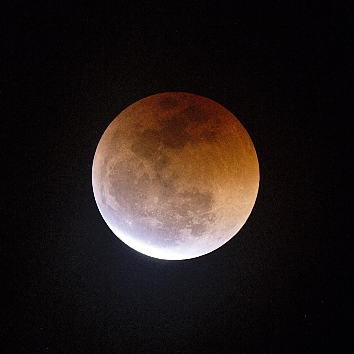 Eclipsi de lluna a punt de sortir de la totalitat
