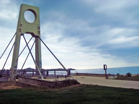 Pont dels ànecs al passeig de Sant Antoni de Calonge amb el mar al fons. La lluna sortirà pel costat dret del port
